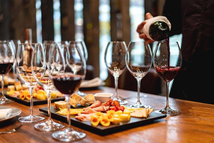 winetasting met glazen rode wijn en hapjes